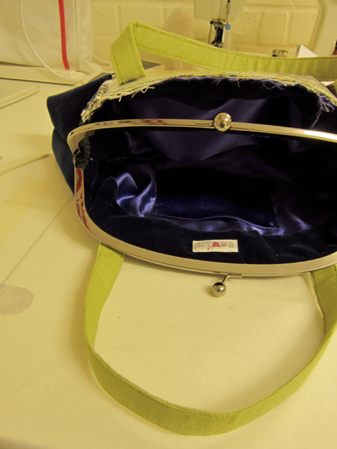kiss lock frame handbag with electicblue lining ,lime green handles under construction with sewin logo visible