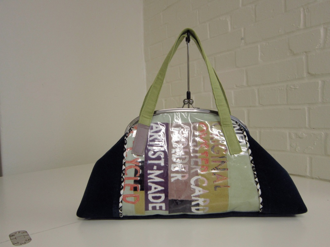 Wearable Handbag Art with hand cut coloured cloth letters from fonts, hand appliqued on mixed fibre patchwork ground, snap close frame ,with dark navy velour sides and reverse,lined in midnight blue satin.
