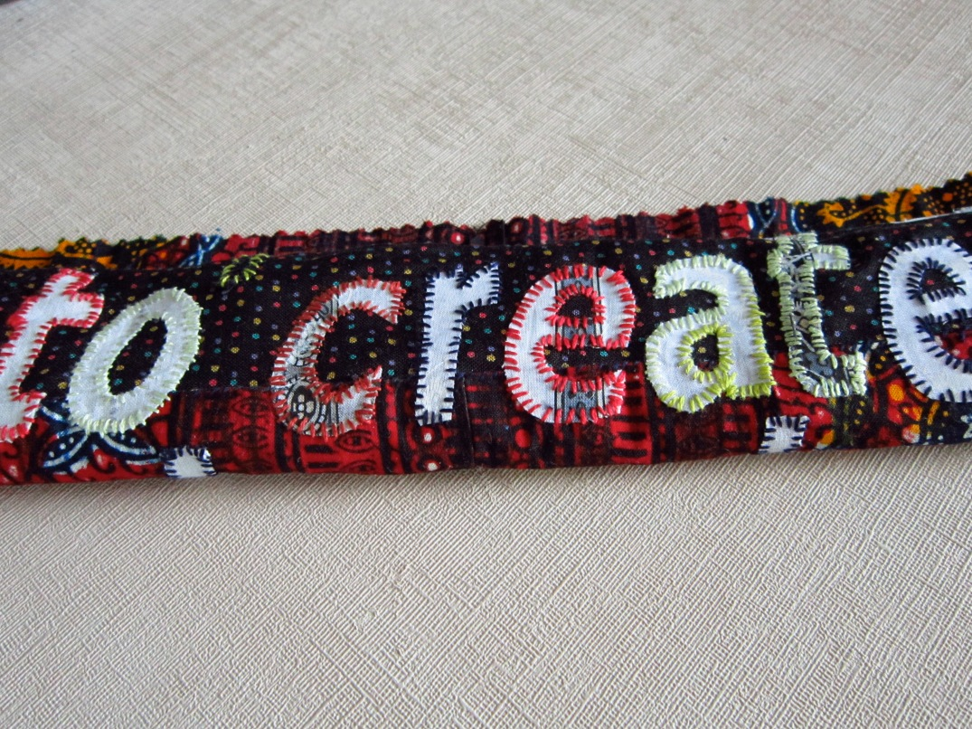 Affirmative art cloth on red/maroon ground with white font and hand embellished with multicoloured thread.