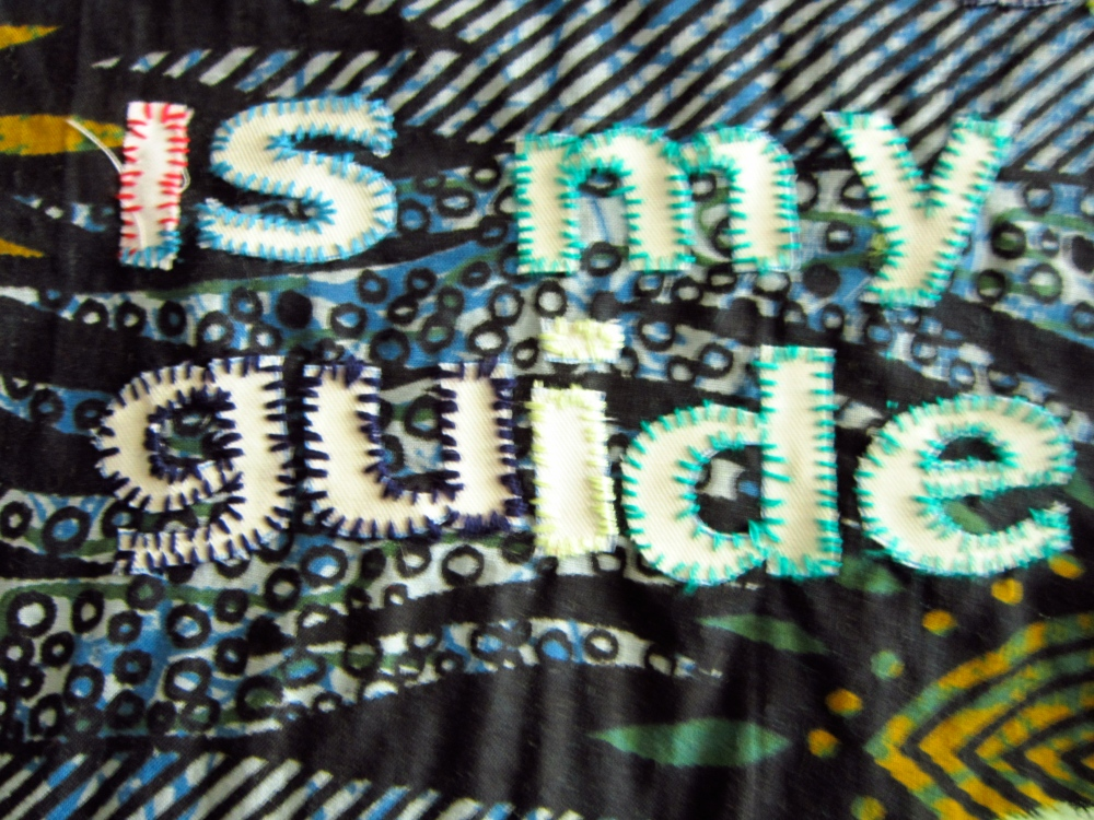 multi coloured Affirmation written in white cloth font appliqued onto blue african background fabric.