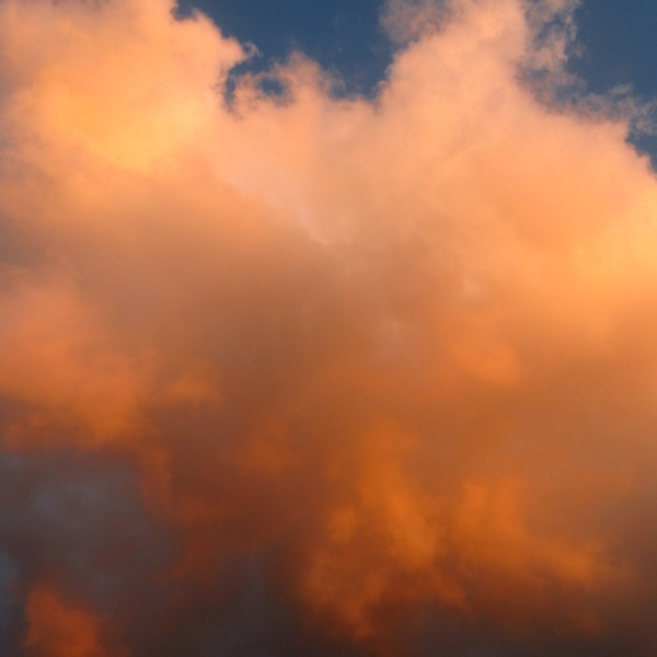 A beautiful voluminous sunset cloud in orange,peach,gold against a brilliant blue sky.
