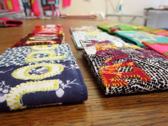 Hand and machine stitched cloth oyster card wallets using affirmations, fonts,art, applique and multi colour thread and fabric.