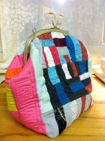 multicoloured improvisational patchwork pieced and quilted purse in mixed fibres, handmade from reloved cloth by Maggie Winnall- Sewin Studio