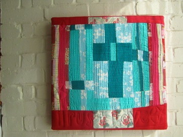 A contemporary art textile in red and green by Maggie Winnall-Sewin Studio.