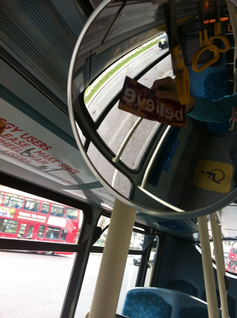 Reflection of 'Believe' Art Oyster Wallet in exit mirror of London bus.