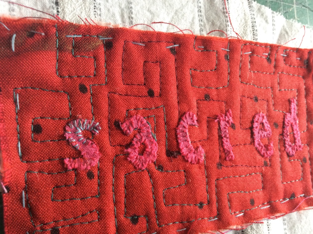 Hand stitched red text in art textile