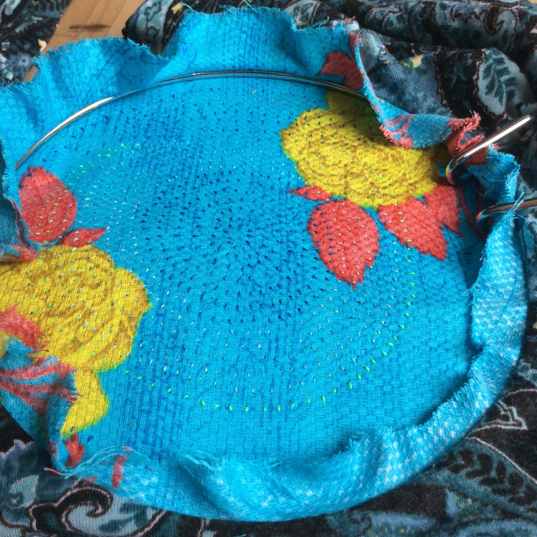 A circular applique world in turquoise with little hand stitches.