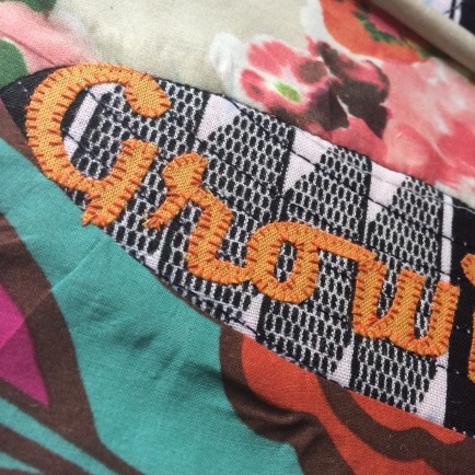 Hand stitched appliqué words with orange thread by Maggie Winnall at Sewin Studio