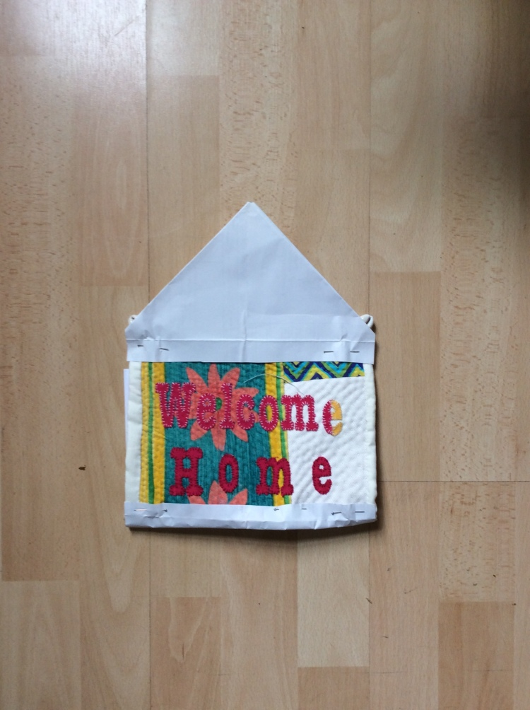 Contemporary hand quilted and stitched textile art with embellished words ' Welcome Home